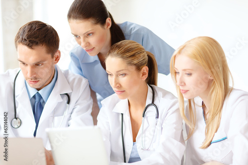 group of doctors with laptop and tablet pc