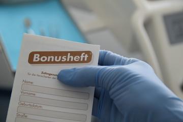 Zahnarzt - Bonusheft in Hand vor Behandlungseinheit