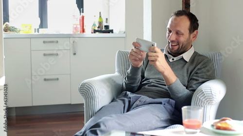Young handsome happy man playing game on smartphone at home