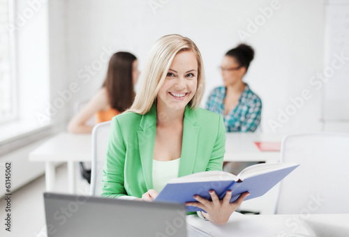 smiling young girl reading book at school