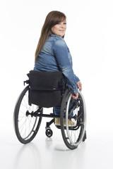 junge Frau im Rollstuhl von hinten