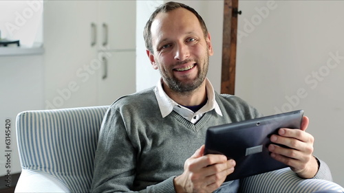 Portrait of young happy man with tablet computer at home