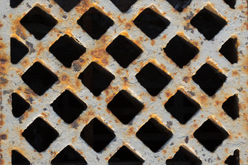 rusty grate in the sidewalk