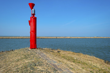 Red beacon on a dike in a lake under a clear sky