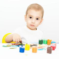 Маленький мальчик учится рисовать