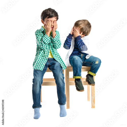 Kids covering his eyes over white background