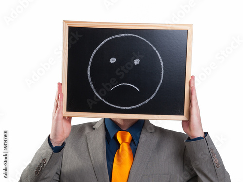 Businessman hiding his face with a white billboard with a sad fa