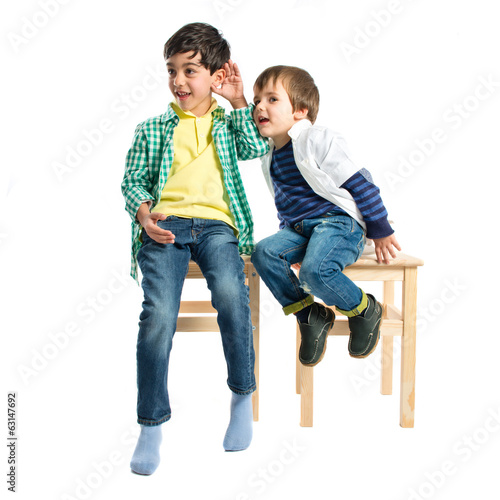 Kids whispering over white background