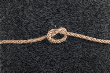 knot of the rope lies on the natural leather