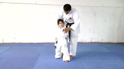 Little girl learning from her karate instructor