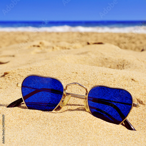 heart-shaped sunglasses in the sand of a beach