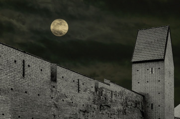 Disturbed night with full moon above old fortress wall