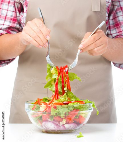 Cook is mixing salad