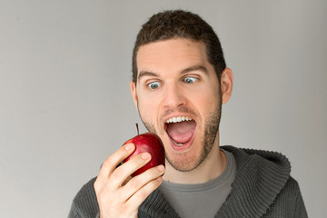 Young man looking at an apple with funny expression