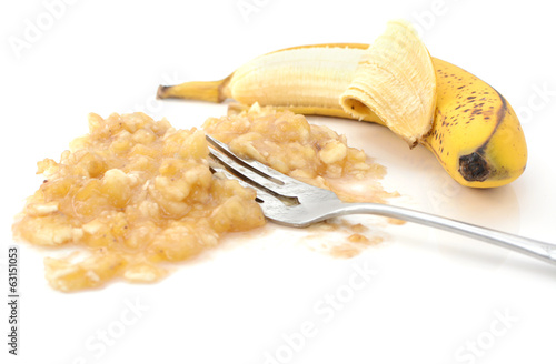 Closeup of half-peeled banana with a fork in mashed puree