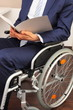 Geschaeftsmann im Rollstuhl mit Dokument