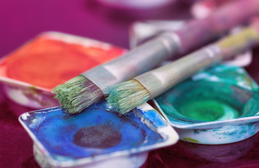 Brushes laying on different paint pots