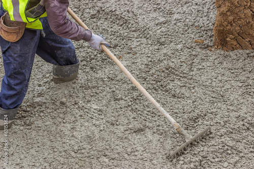 Builder worker standing in fresh cement, using a metal rake to f