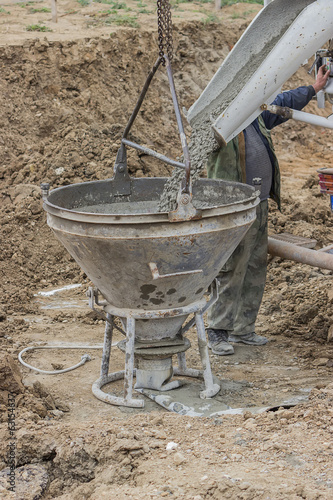 Builder worker filling concrete funnel