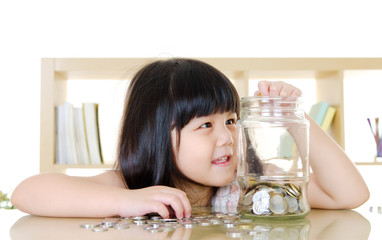 Little girl putting coins into the glass bottle.