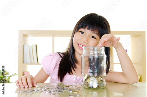 Asian girl putting coins into the glass bottle.
