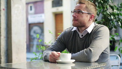 Man drinking coffee in street restaurant and relaxing.