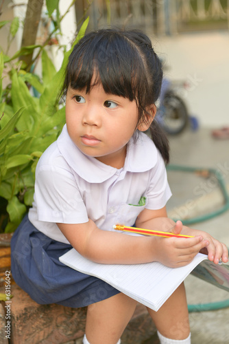 Cute asian child tired of homework at home.
