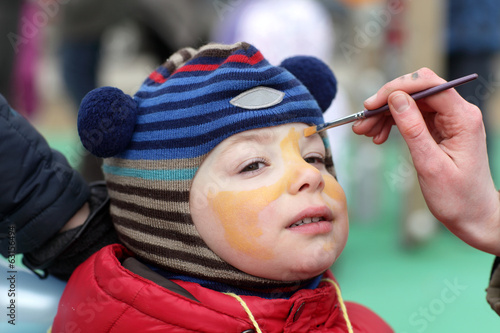 Woman painting kid face