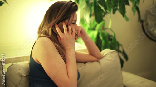 Woman talking on cellphone at night on sofa in room.