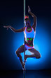 Graceful young pole dancer with fluorescent makeup