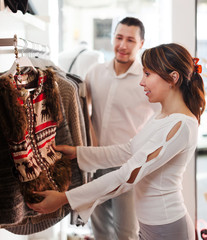 couple choosing jacket at clothing shop