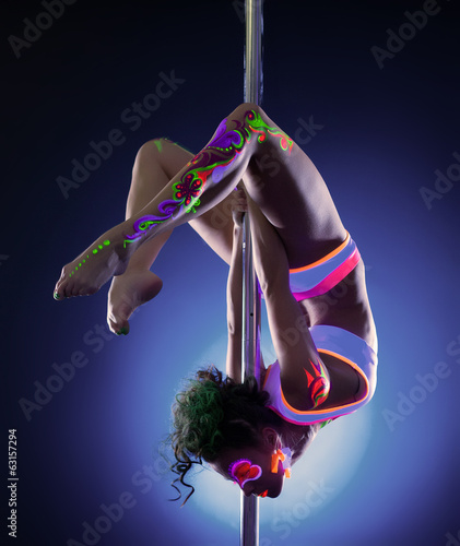 Pretty girl posing hanging upside down on pylon