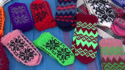 pairs of multicolored knitted mittens in market