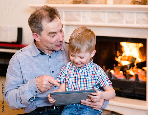 Happy boy and his grandfather using a tablet computer