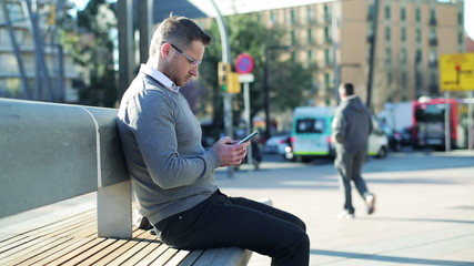 Man sitting on street bench and using cellphone