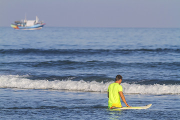 Surfer with his surfboard at the Balanfan beach.Bali.Indonesia