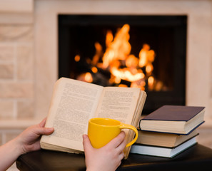 hands holding open book and cup of coffee near the fireplace