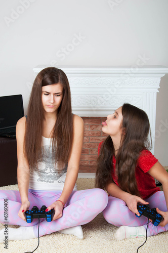 Two sisters are playing a game console