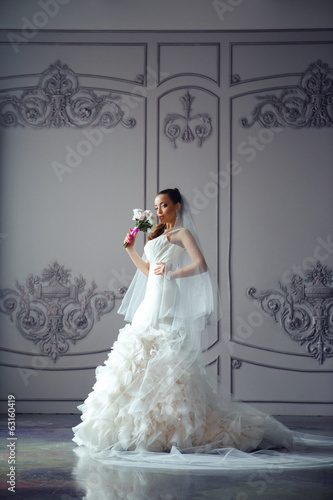 Portrait of bride in beautiful wedding dress with bouquet