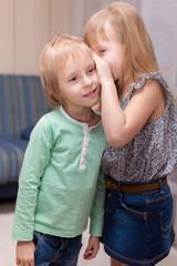 girl is whispering something to boy