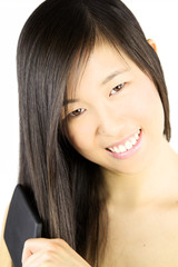 Smiling asian american woman with brush in hand