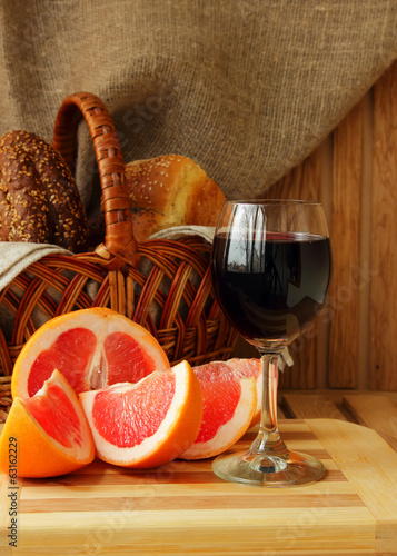 Glass of wine, grapefruit and a basket of bread