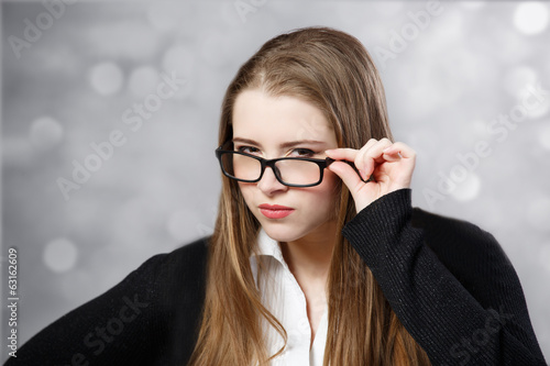 Girl with glasses staring eyes at light background