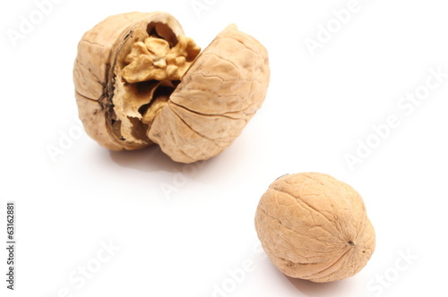 Two walnuts - whole and opened on white background
