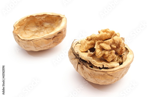 Opened fresh walnut and shell in background. White background