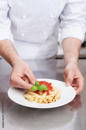 Male chef completing pasta..
