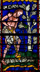 Stained glass window of Adam working