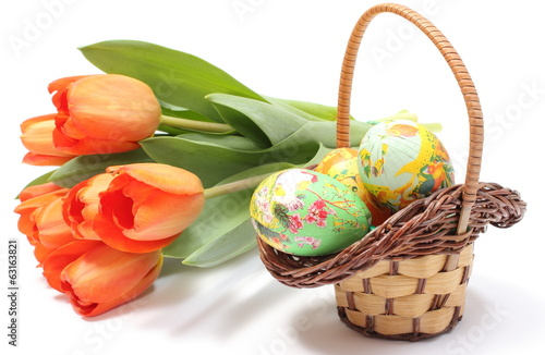 Colorful Easter eggs in wicker basket and fresh tulips