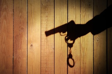 Male Hand with Gun and Handcuffs on Natural Wood Background, XXX