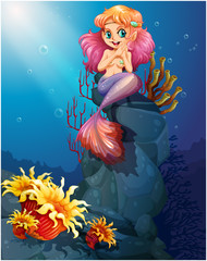 A smiling mermaid sitting above the rocks